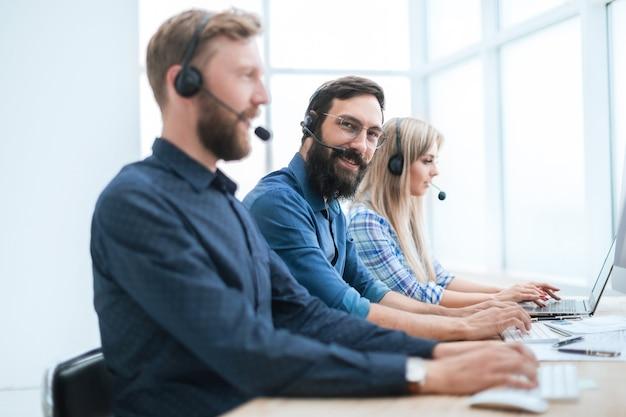 Avvicinamento. il personale professionale del call center utilizza i computer per lavorare con i clienti.