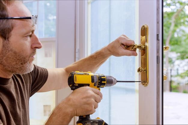 Primo piano di un fabbro professionista che installa o ripara una nuova serratura con catenaccio