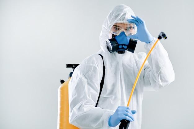 Avvicinamento. disinfettante maschile professionale in una tuta protettiva. foto con copia-spazio.