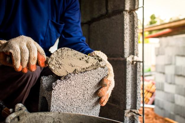 Primo piano di un lavoratore professionista che utilizza un coltello da padella per costruire un muro di mattoni con mattoni di cemento e cemento. idee imprenditoriali e industria delle costruzioni