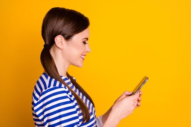 Close-up profilo vista laterale ritratto di bella attraente bella bella allegra focalizzata ragazza dai capelli castani utilizzando dispositivo navigazione web isolato su sfondo di colore giallo brillante brillante brillantezza vibrante