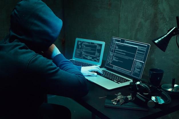 Primo piano del programmatore delle mani dell'hacker che digita un codice