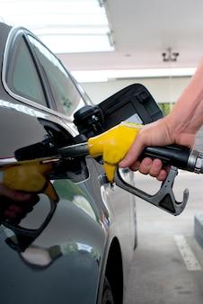 Primo piano che pompa benzina sulla macchina nera