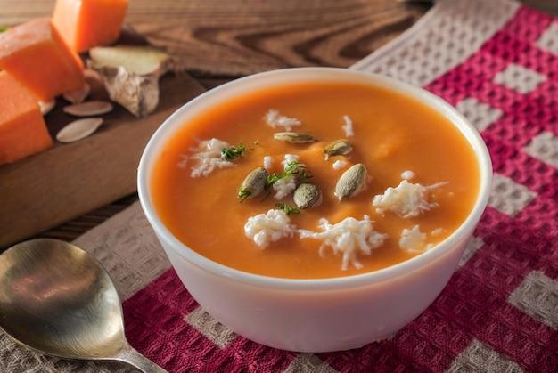 Close-up zuppa di crema piccante di zucca con formaggio e semi su un tavolo di legno su una tovaglia rossa.