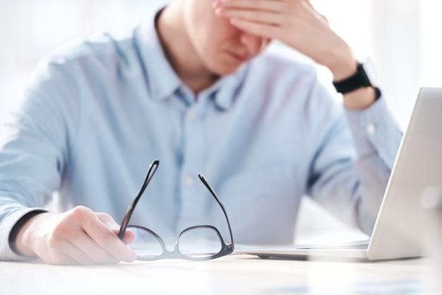 Primo piano dell'uomo d'affari perplesso che si siede davanti al computer portatile e che sente l'emicrania dall'esaurimento in ufficio