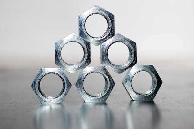 Primo piano di una piramide di cinque dadi in metallo cromato a forma di favi uno accanto all'altro