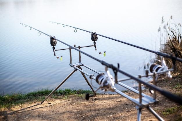 Primo piano di cremagliera con canne da pesca in riva al lago, pescatore in attesa di pesci d'acqua dolce, pesca, pesca sportiva
