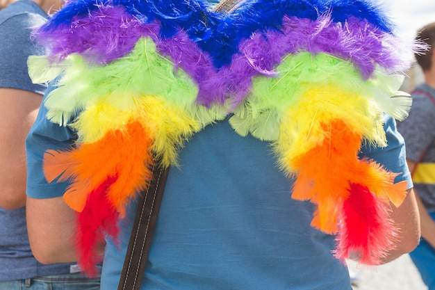 Primo piano sulle ali arcobaleno sulla schiena dell'uomo persone alla parata annuale del gay pride