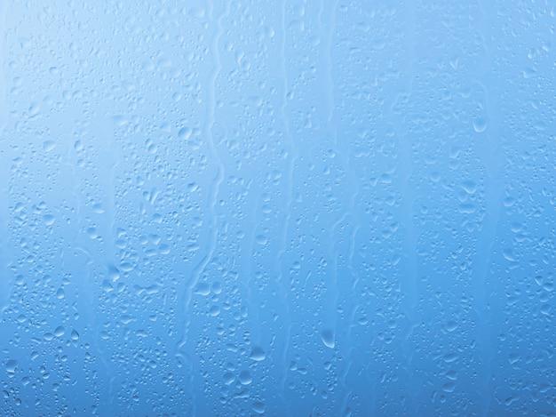 Chiudere le gocce di pioggia e l'acqua scorre sulla superficie del vetro della finestra su sfondo grigio e blu del cielo in una giornata piovosa