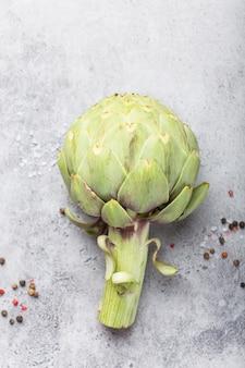 Close-up di crudo carciofo fresco con condimenti pronti da cucinare, ottimo come cibo vegetariano o ingrediente per salutari insalate e diete, pietra grigia sfondo rustico