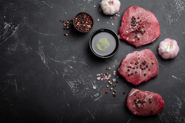 Primo piano di bistecca di carne marmorizzata fresca cruda su fondo di cemento rustico scuro con sale e pepe, olio d'oliva, aglio pronto per essere cucinato. cucinare il concetto di carne con spazio per il testo, vista dall'alto