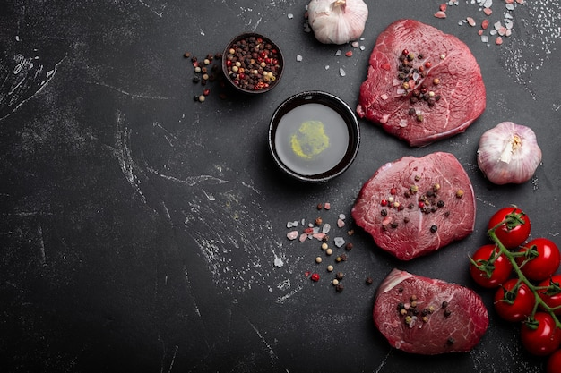 Primo piano di bistecca di carne marmorizzata fresca cruda su fondo di cemento rustico scuro con condimenti, olio d'oliva, aglio, pomodori pronti per essere cucinati. cucinare il concetto di filetto di carne con spazio per il testo, vista dall'alto