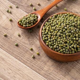 Chiuda in su del fagiolo verde crudo in una ciotola sul fondo della tavola di legno.