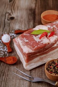 Primo piano del pezzo di pancia di maiale crudo su una superficie di legno con spezie ed erbe aromatiche