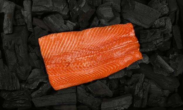 Close up filetto di pesce salmone crudo su pezzi di carbone di legna grumo nero pronto per barbecue, vista dall'alto, direttamente sopra