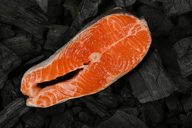 Primo piano bistecca di pesce salmone crudo su pezzi di carbone di legna grumo nero pronto per barbecue, vista dall'alto, direttamente sopra