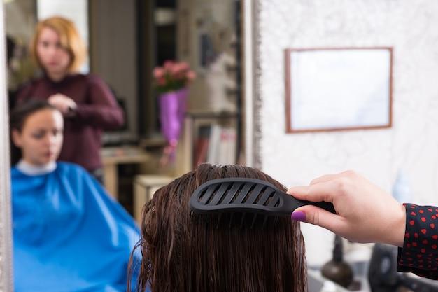 Close up vista posteriore dello stilista utilizzando la spazzola per pettinare i capelli bagnati di bruna donna seduta in poltrona in salone con riflesso sfocato sullo specchio di sfondo