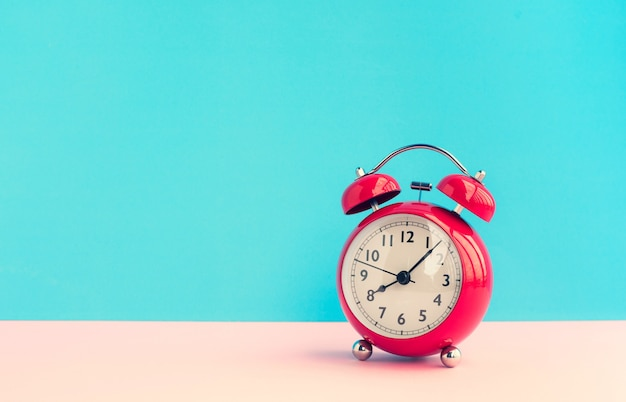 Chiudere la sveglia rossa su sfondo blu pastello concetti di temporizzazione