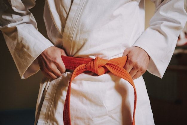 Chiuda sulla fascia rossa su bianco del combattente di arti marziali