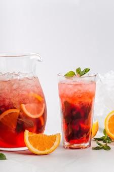 Primo piano sulla limonata ai frutti di bosco in una brocca e vetro isolato