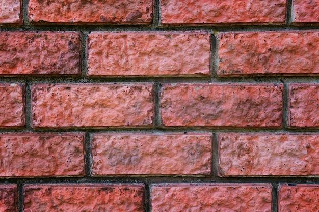 Una chiusura di un muro di mattoni rossi. trama mattone. sfondo snodato in muratura. cuciture di un muro di mattoni. blocchi di mattoni nella costruzione di recinzioni. zoom di una struttura muraria in mattoni.