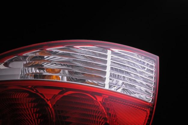 Primo piano dei fari delle auto rosse sullo sfondo nero isolato. faro dell'auto tagliato