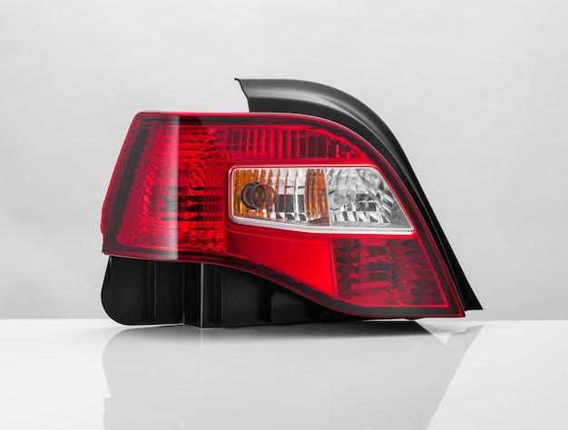 Primo piano di un fanale posteriore di un'auto rossa su uno sfondo chiaro con riflessione. isolato