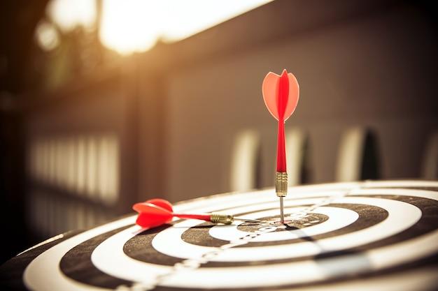 Primo piano la freccia rossa del dardo che colpisce il centro del bullseye.