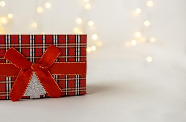 Primo piano di una confezione regalo rossa su sfondo bianco con un bokeh con un posto per il testo