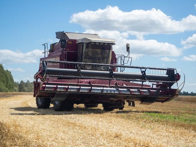 Primo piano di una mietitrice rossa che guida attraverso un campo per la raccolta. concetto di agricoltura