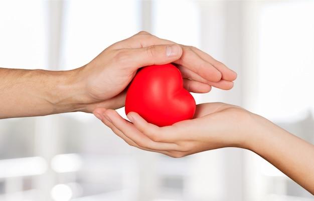Cuore rosso del primo piano in mani, concetto di amore
