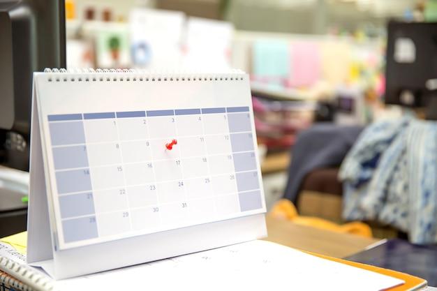 Primo piano un perno rosso sul calendario da tavolo vuoto.