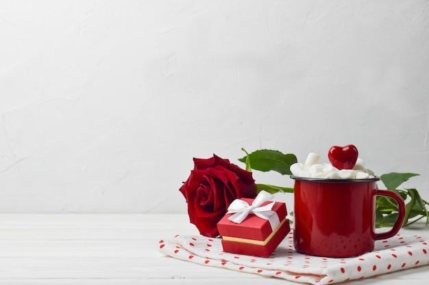 Primo piano di una rosa rossa con un regalo e una tazza di metallo rossa. Foto Premium