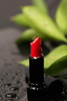 Primo piano di rossetto rosso saturo con gocce d'acqua.