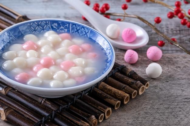 Primo piano di tangyuan rosso e bianco (tang yuan, polpette di riso glutinoso) nella ciotola blu. cibo del festival del solstizio d'inverno.