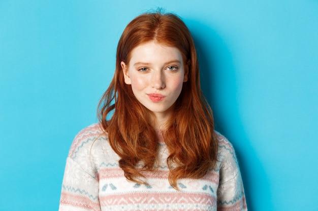 Primo piano della ragazza astuta rossa che ha un'idea, sorride e fissa la telecamera soddisfatta del piano, in piedi su sfondo blu.