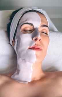Primo piano di giovane donna rilassata sdraiata con trattamento maschera facciale nella spa. medicina, sanità e concetto di bellezza.