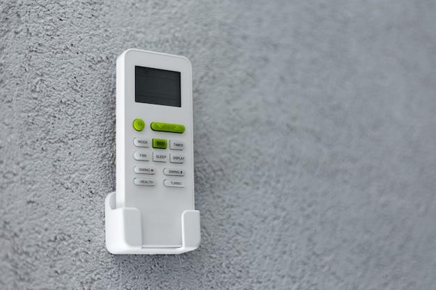 Primo piano del telecomando del condizionatore d'aria in piedi sul supporto, sulla parete strutturata di grigio. sfondo con copia spazio.