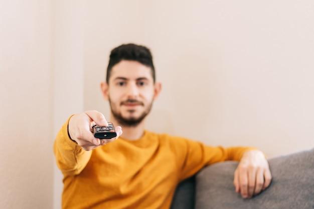 Primo piano di un telecomando nella mano di un uomo degli anni '30 che guarda la tv in streaming sul divano della sua camera da letto.