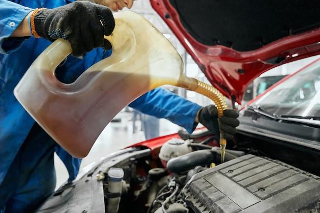 Chiuda in su delle mani del riparatore in guanti neri mantenendo la bombola, sostituendo e versando olio fresco nel motore dell'auto rossa. manutenzione auto, cambio e rifornimento di liquidi gialli