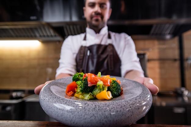 Primo piano dello chef del ristorante che mostra insalata di verdure sul bellissimo piatto con struttura in pietra