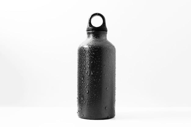 Primo piano della bottiglia termica riutilizzabile in alluminio spruzzata con acqua, di colore nero