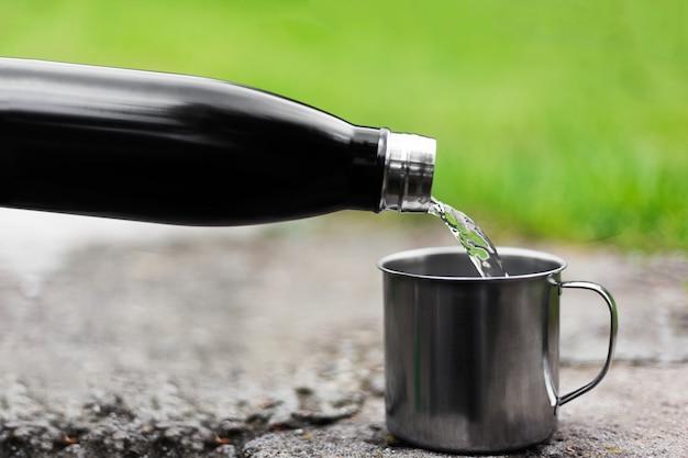 Il primo piano della bottiglia termica d'acciaio riutilizzabile versa l'acqua nella tazza d'argento sull'erba verde nel bokeh