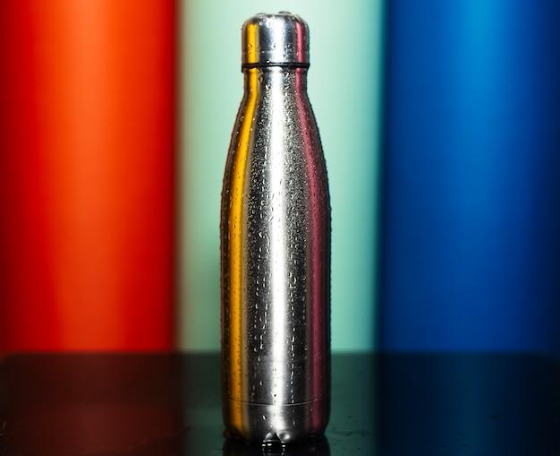 Primo piano della bottiglia termica in acciaio riutilizzabile spruzzata con acqua sulla parete di lava lussureggiante, aqua menthe e blu fantasma di colore.