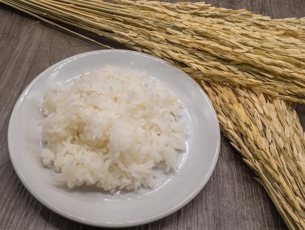 Chiuda su riso in piatto bianco su fondo di legno grigio e risone secco, pianta di riso