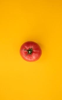 Close up pomodoro maturo su sfondo giallo brillante vista dall'alto laici piatta. fondo astratto di estate con il pomodoro