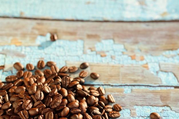 Close up chicchi di caffè tostati sul tavolo e copia spazio.