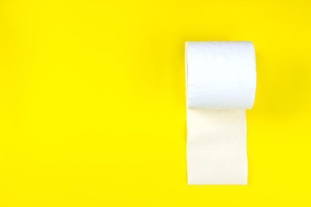 Close up rotolo di carta igienica su sfondo giallo. copia spazio.