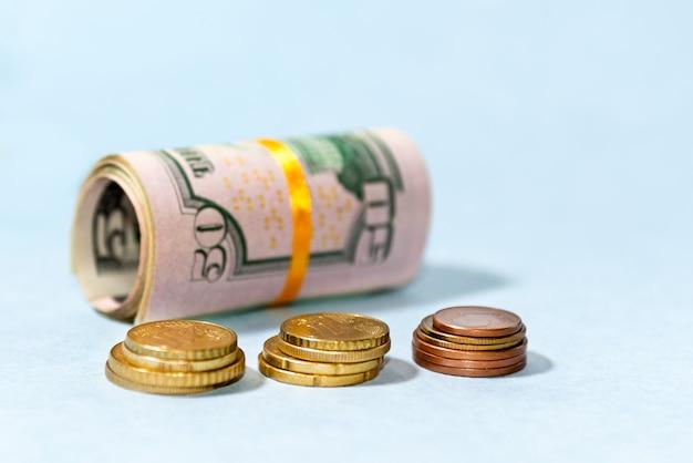 Close-up di banconote in dollari americani e monete in euro arrotolate