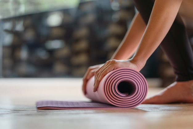 Stuoia di yoga rotolamento primo piano dopo l'allenamento in palestra, sport e palestra.